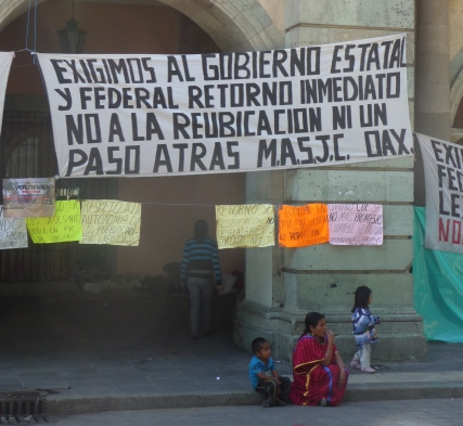 Triqui woman in red traditional dress with her children at the Triqui protest camp in Oaxaca City