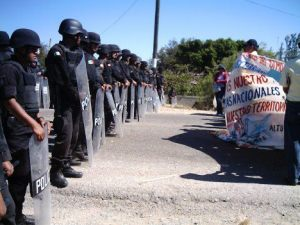 Protesters calling for the expulsion of transnational companies are met by a police line in Oaxaca,Mexico. Photo courtesy of oaxacaentrelineas.com