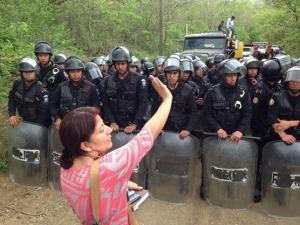 Yolanda Oqeili faces riot police during the May eviction at La Puya protest camp