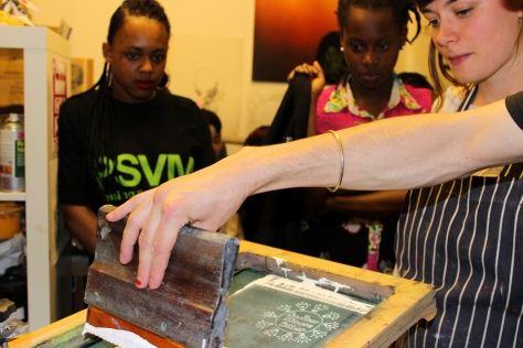 Banister House Solar Co-op interns learn how to screen print promotional t-shirts